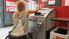 Bild zeigt Frau im Rollstuhl vor einem barrierefreien Geldautomat