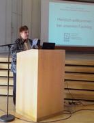 Bild zeigt die Veranstalterin Angela Rubens auf der Bühne beim Halten ihres Vortrages