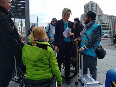 Bild zeigt Menschen mit und ohne Behinderung im Gespräch mit der DB vor dem DB-Tower bei der Kundgebung