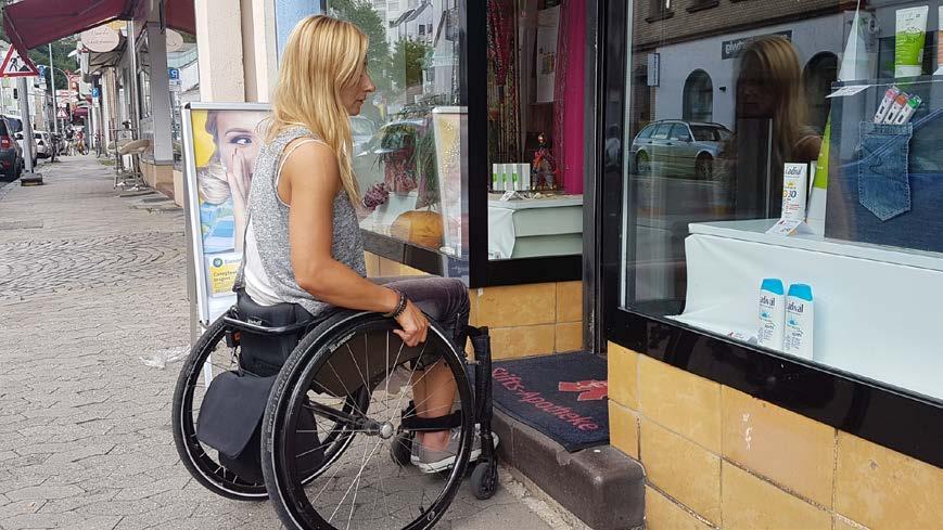Bild zeigt Rollstuhlfahrerin Dunja Fuhrmann vor dem Eingang der Apotheke, die nur über eine Stufe erreichbar ist