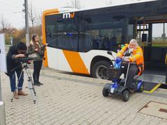 Bild zeigt einen Scooter-Fahrer aus dem Bus heraus fahren. Links daneben steht der Kameramann und die Ton-Frau
