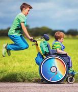 Bild zeigt ein Beispielfoto von einem Kind im Rollstuhl, welches von einem anderen Kind geschoben wird