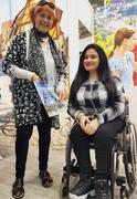 Foto zeigt Ilse Schwarz mit einer Standbesucherin im Rollstuhl. Frau Schwarz hält einen Reisekatalog in der Hand