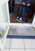Bild zeigt einen Rollstuhl vor der Balkontür, die eine Schwelle hat
